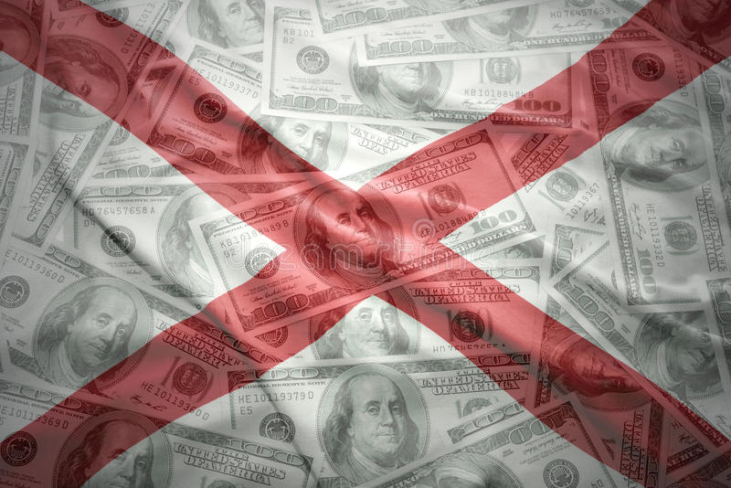 Bandera colorida del estado de Alabama que agita en un fondo americano del dinero del dólar fotos de archivo