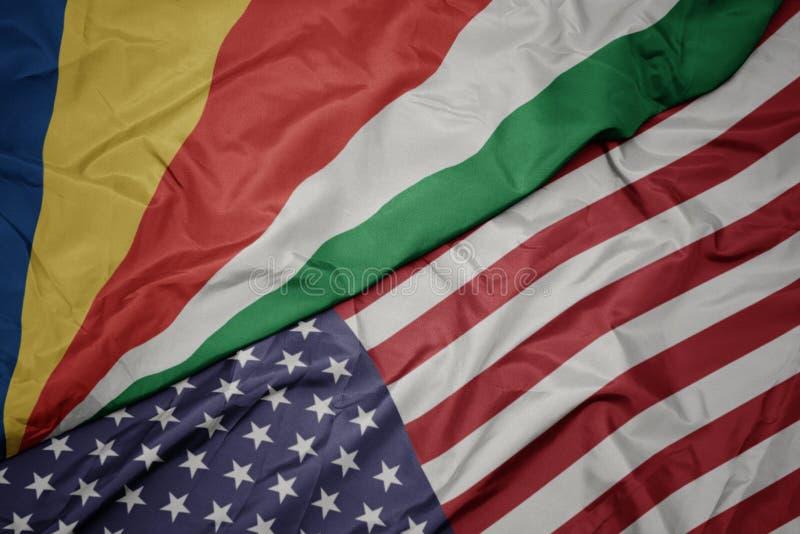 bandera colorida que agita de los Estados Unidos de América y bandera nacional de Seychelles imágenes de archivo libres de regalías