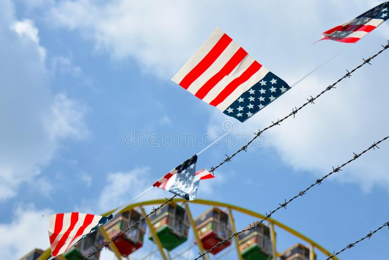 Bandera con colores americanos con las rayas rojas y las estrellas blancas en el fondo azul que cuelga al lado de una cerca del a fotos de archivo libres de regalías