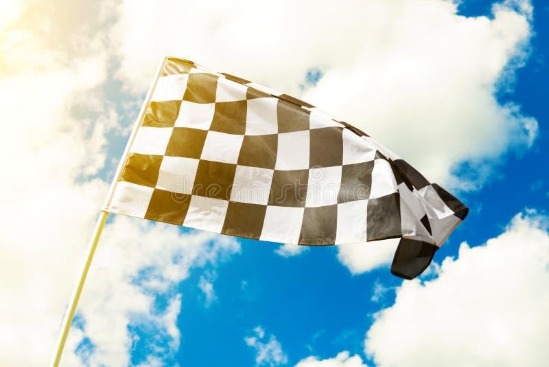 Bandera a cuadros que agita en el viento con la llamarada del sol vista fotos de archivo