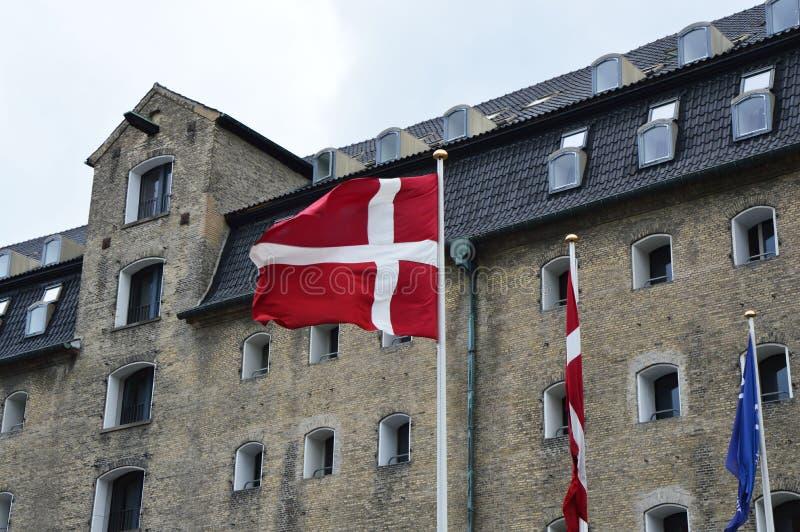Bandera danesa que agita con el almirante Hotel en el fondo, Copenhague, Dinamarca imagenes de archivo