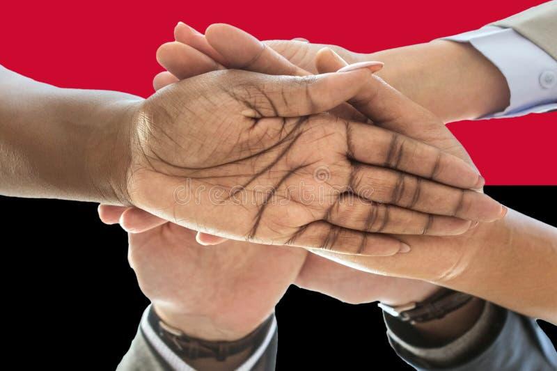Bandera de Angola, integración de un grupo multicultural de gente joven imagenes de archivo