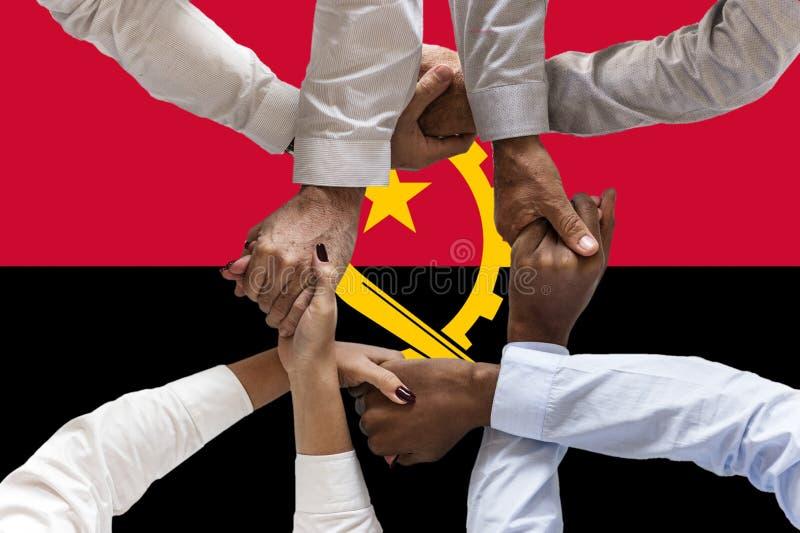 Bandera de Angola, integraci?n de un grupo multicultural de gente joven fotografía de archivo libre de regalías