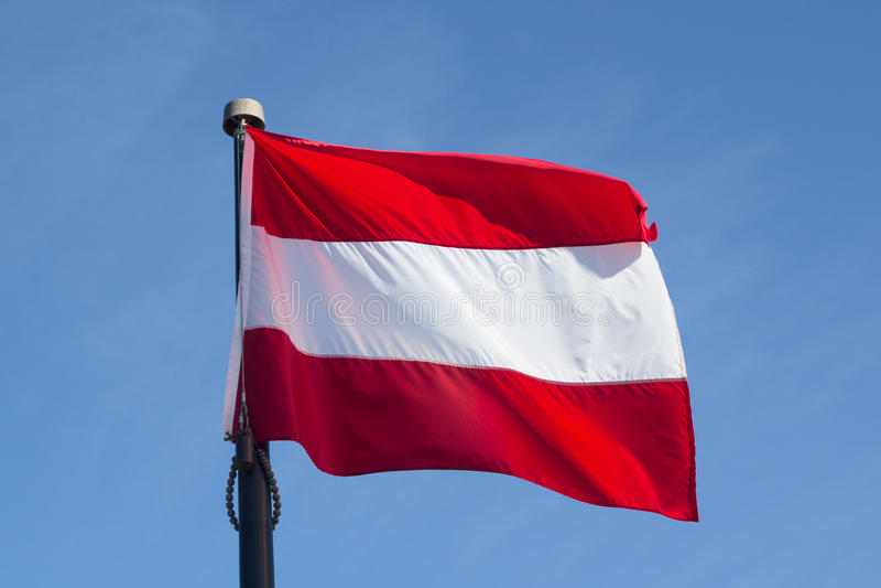 Bandera de Austria contra Windy Blue Sky imagen de archivo