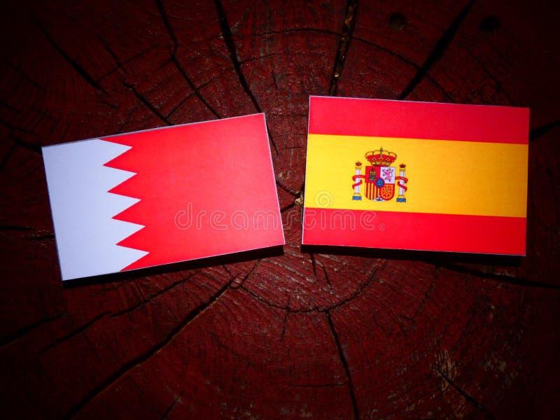 Bandera de Bahrein con la bandera española en un tocón de árbol foto de archivo libre de regalías