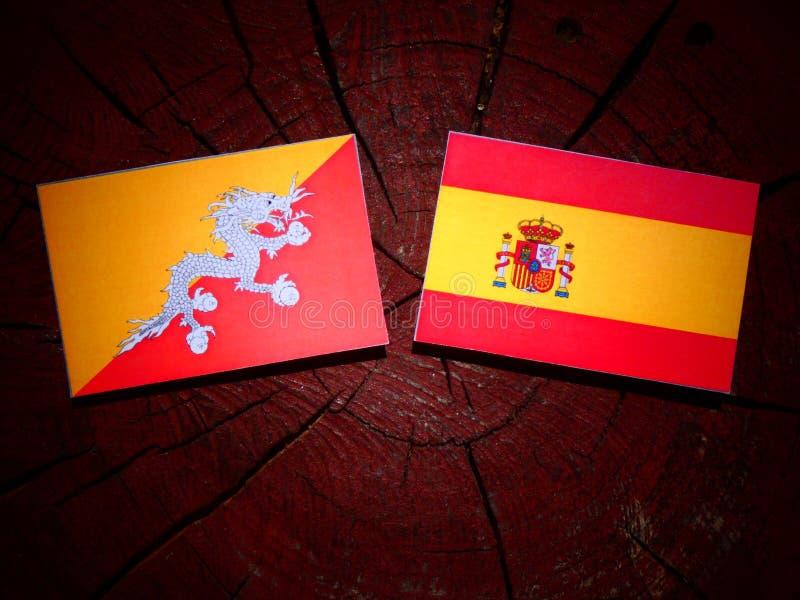 Bandera de Bhután con la bandera española en un tocón de árbol fotografía de archivo libre de regalías