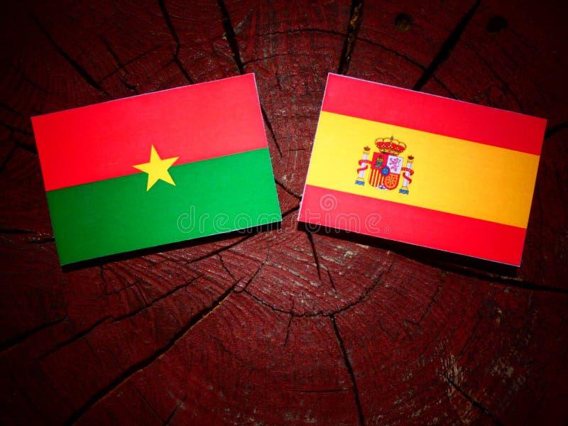 Bandera de Burkina Faso con la bandera española en un tocón de árbol fotografía de archivo