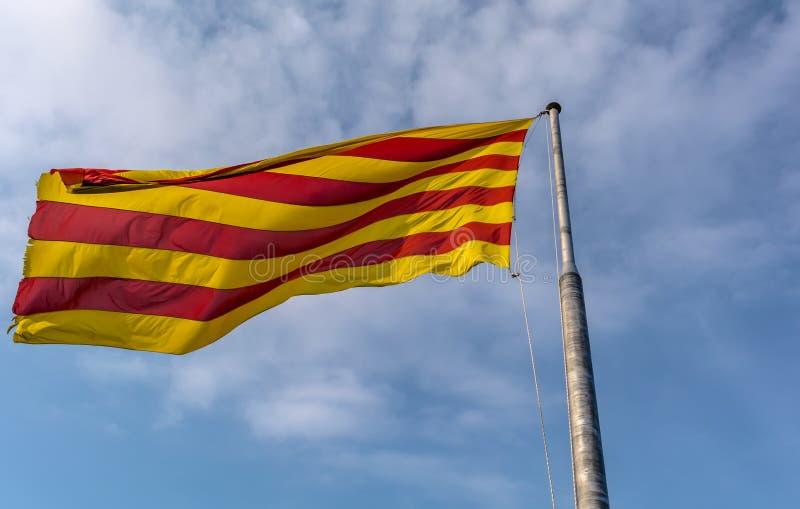 Bandera de Cataluña que agita en la brisa contra el cielo azul imagen de archivo libre de regalías