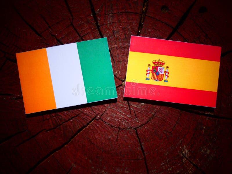 Bandera de Costa de Marfil con la bandera española en un tocón de árbol foto de archivo libre de regalías