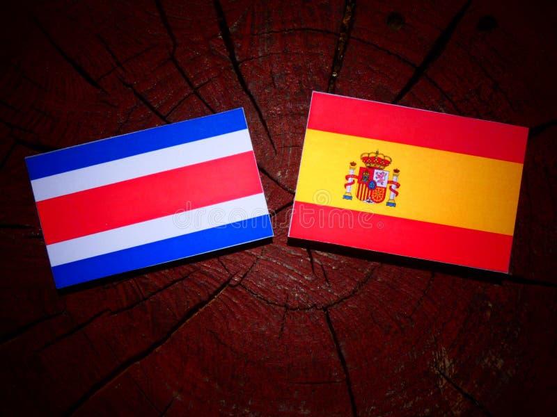 Bandera de Costa Rican con la bandera española en un tocón de árbol foto de archivo libre de regalías