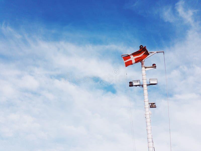 Bandera de Dinamarca en el partido de la nave en el fondo del cielo azul imágenes de archivo libres de regalías
