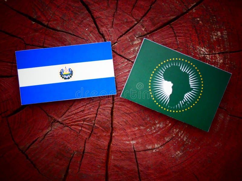Bandera de El Salvador con la bandera de unión africana en un aislante del tocón de árbol imagen de archivo libre de regalías
