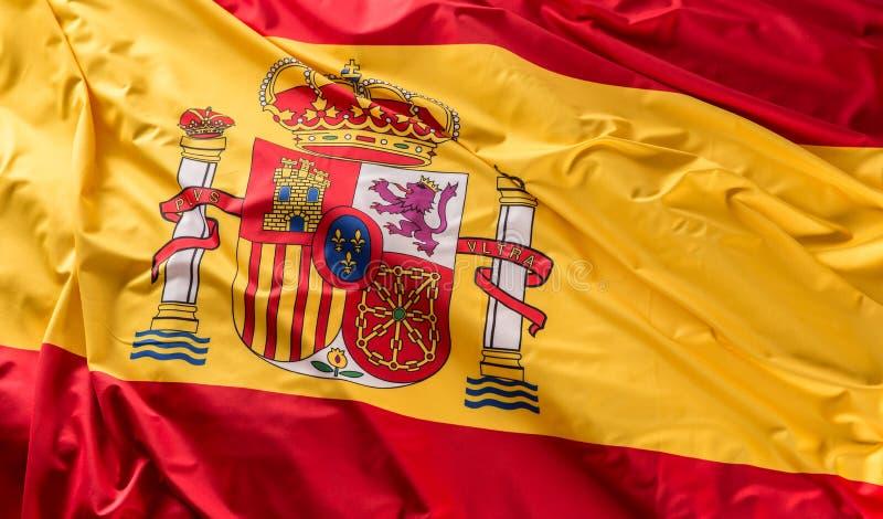 Bandera de España de la seda Colores nacionales españoles con el emblema imagenes de archivo