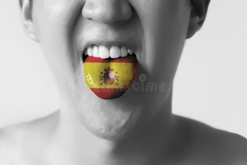 Bandera de España pintada en lengua de un hombre - indicando lengua española y hablando n blanco y negro fotografía de archivo libre de regalías
