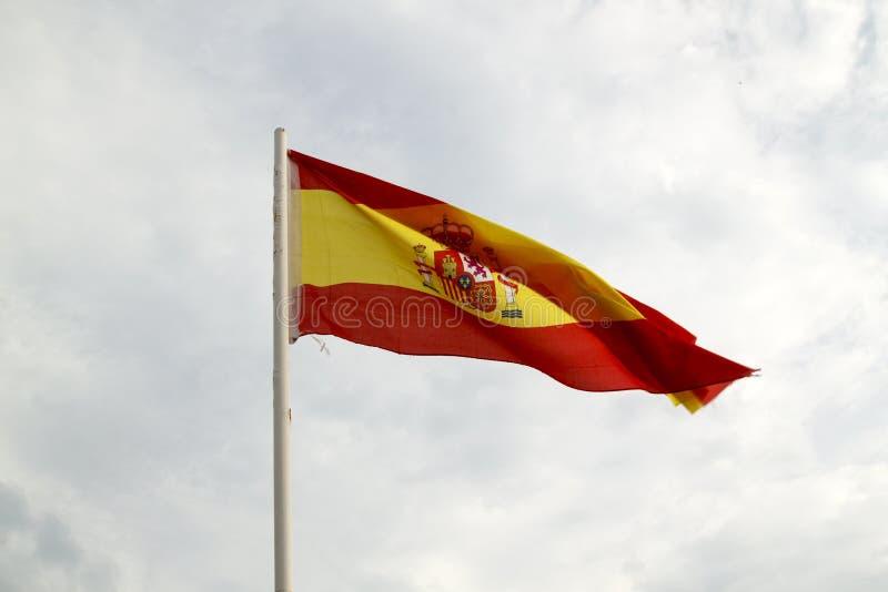 Bandera de Espa?a en un cielo azul con el fondo de las nubes fotografía de archivo libre de regalías