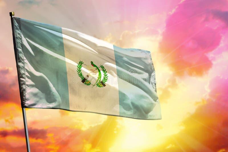 Bandera de Guatemala que agita en fondo colorido hermoso de la puesta del sol o de la salida del sol Diversa bola 3d imagen de archivo libre de regalías