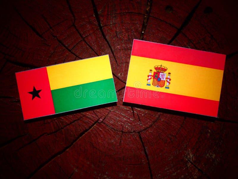 Bandera de Guinea-Bissau con la bandera española en un tocón de árbol imagen de archivo
