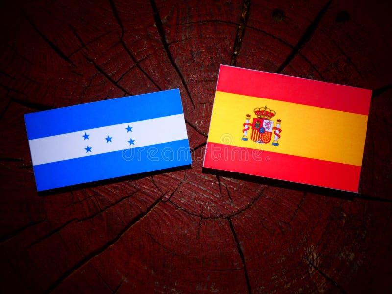 Bandera de Honduras con la bandera española en un tocón de árbol fotos de archivo