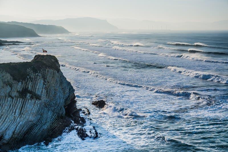 Bandera de Ikurrina con las ondas ventosas en la playa de Sopelana imagenes de archivo