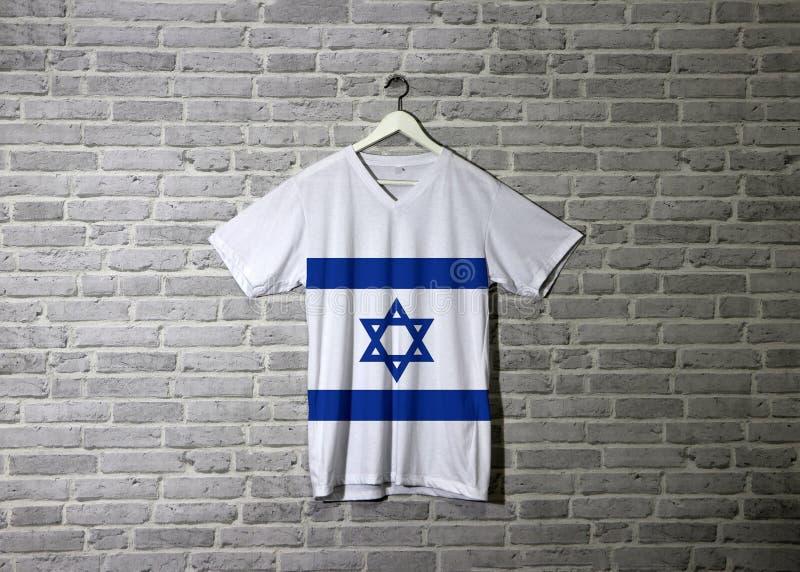 Bandera de Israel en la camisa y colgante en la pared con el papel pintado del modelo del ladrillo, hexagram azul en un fondo bla fotos de archivo