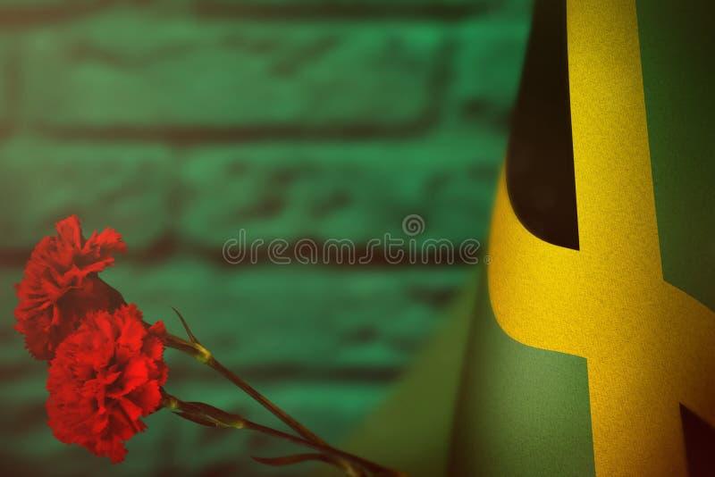 Bandera de Jamaica para el honor del día o del Memorial Day de veteranos con dos flores rojas del clavel Gloria a los héroes de J fotografía de archivo