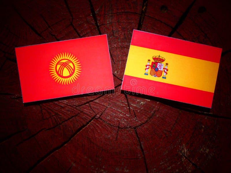 Bandera de Kirguistán con la bandera española en un tocón de árbol imagenes de archivo