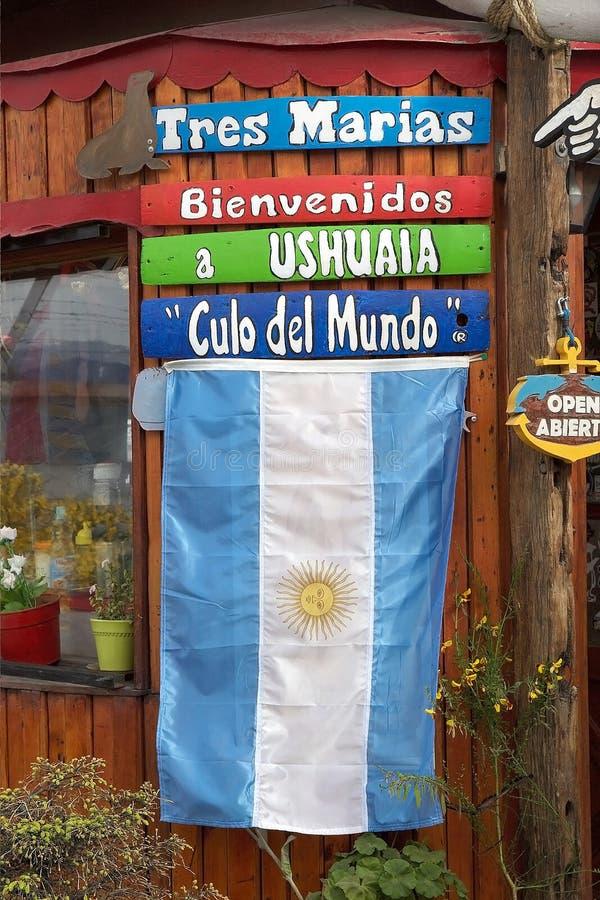 Bandera de la Argentina en la entrada de una agencia turística en Ushuaia, la Argentina fotografía de archivo libre de regalías