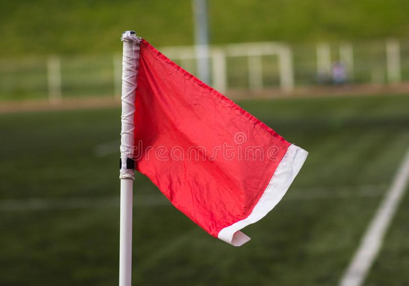 Bandera de la esquina roja en un fondo de un campo de fútbol borroso imagen de archivo libre de regalías