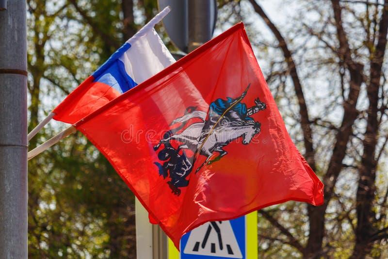 Bandera de la Federación Rusa y bandera de la ciudad de Moscú ondeando al viento contra árboles a la luz del sol fotografía de archivo