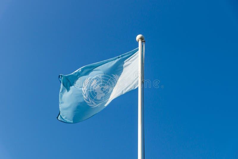 Bandera de la O.N.U de Naciones Unidas con el sunslight en el cielo azul despejado en el cementerio conmemorativo de Naciones Uni fotos de archivo