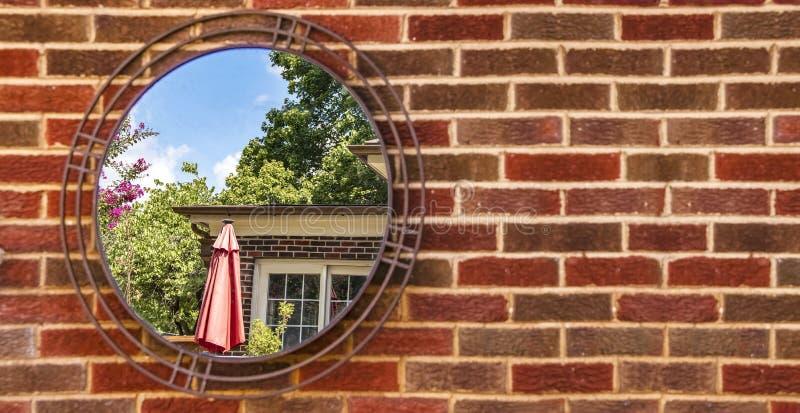 Bandera de la pared de ladrillo borrosa con la ejecución del espejo en ella casa y patio y árboles reflectores y cielo azul de la imagen de archivo libre de regalías