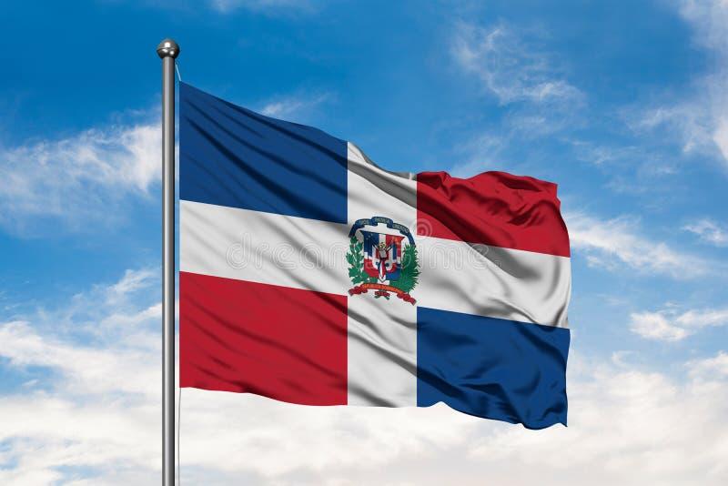 Bandera de la República Dominicana que agita en el viento contra el cielo azul nublado blanco Bandera dominicana foto de archivo