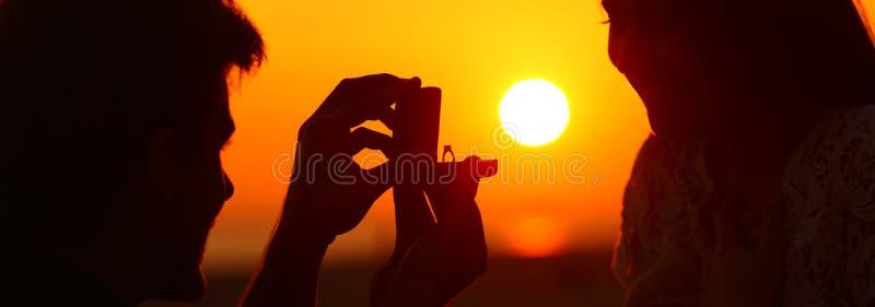 Bandera de la silueta de la propuesta de matrimonio en la puesta del sol fotografía de archivo