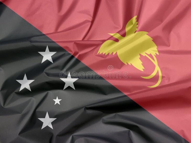 Bandera de la tela de Papúa Nueva Guinea Pliegue del nuevo fondo de la bandera de Papua imagen de archivo libre de regalías