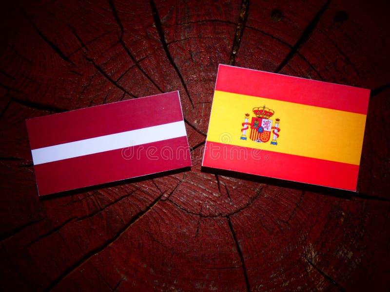 Bandera de Letonia con la bandera española en un tocón de árbol imagenes de archivo