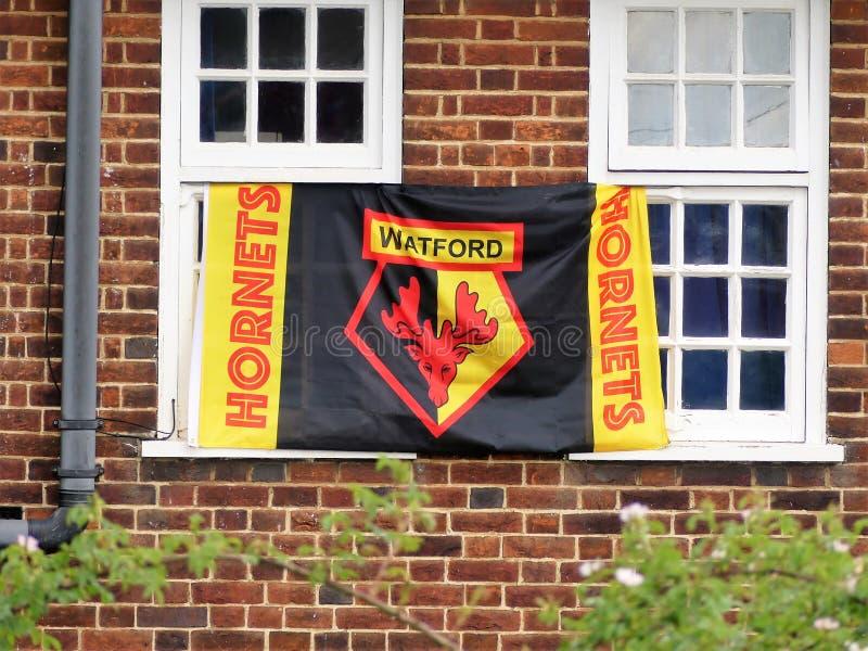 Bandera de los partidarios del club del fútbol de Watford atada a los marcos de ventana fotografía de archivo