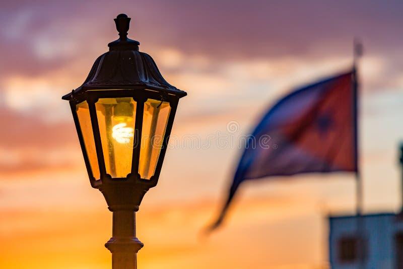 Bandera de los posts y del cubano de la lámpara en la salida del sol fotos de archivo