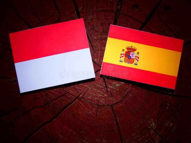 Bandera de Mónaco con la bandera española en un tocón de árbol imagenes de archivo