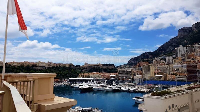 Bandera de Mónaco en la terraza del hotel, alquiler del alojamiento en la ciudad costera para los turistas fotos de archivo