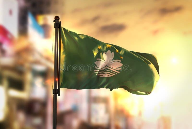 Bandera de Macao contra fondo borroso ciudad en el contraluz de la salida del sol fotografía de archivo