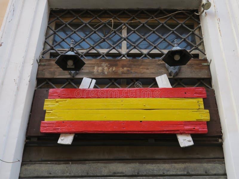 Bandera de madera española antes de una ventana imagen de archivo