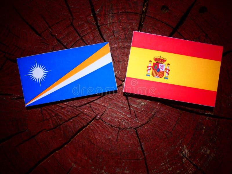 Bandera de Marshall Islands con la bandera española en un tocón de árbol imagen de archivo