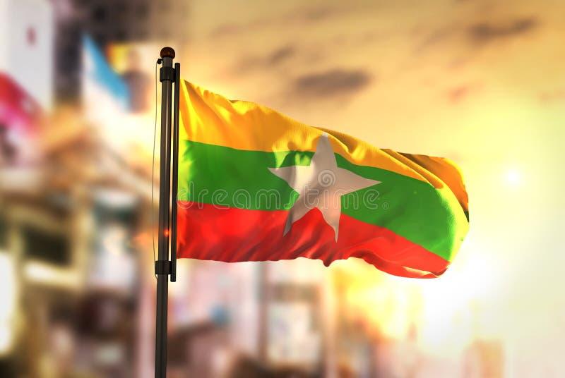 Bandera de Myanmar contra fondo borroso ciudad en la salida del sol Backligh fotos de archivo libres de regalías