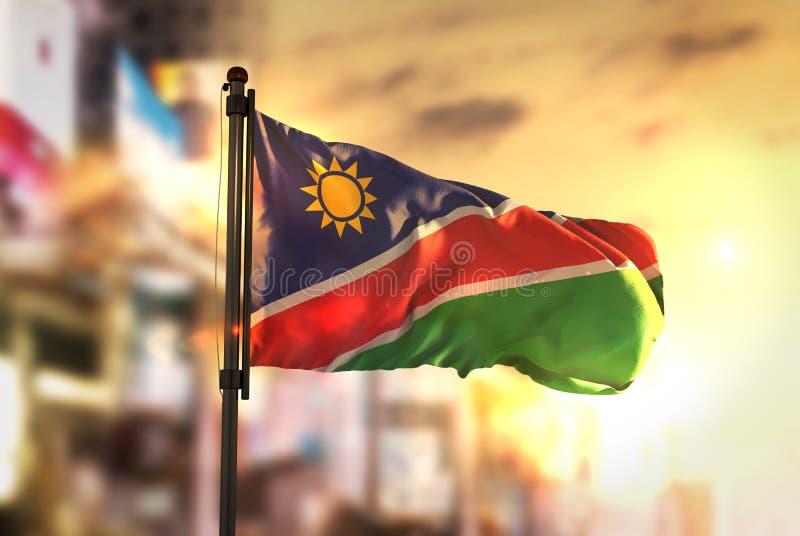Bandera de Namibia contra fondo borroso ciudad en la salida del sol Backligh fotos de archivo