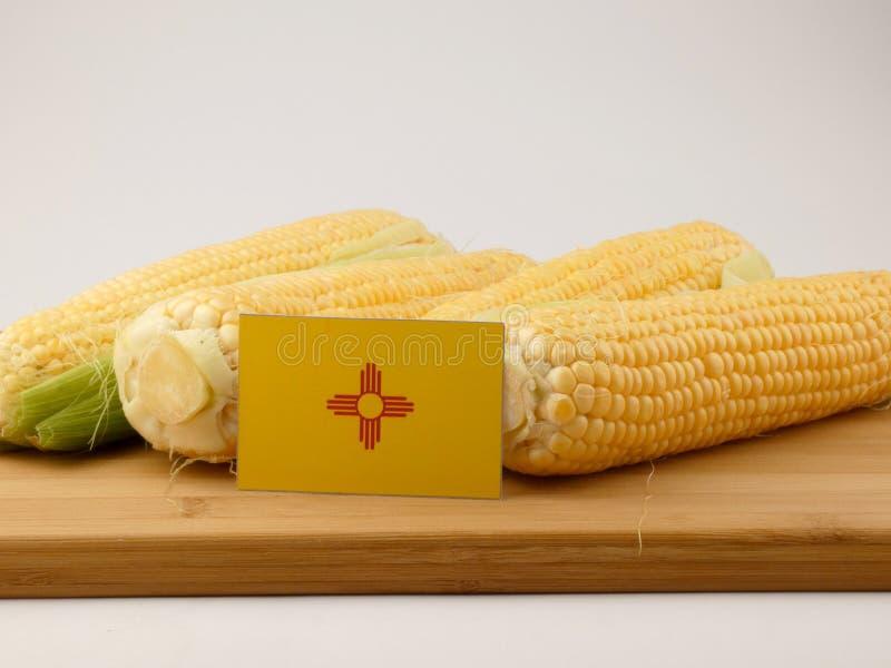 Bandera de New México en un panel de madera con el maíz aislado en un blanco imagen de archivo