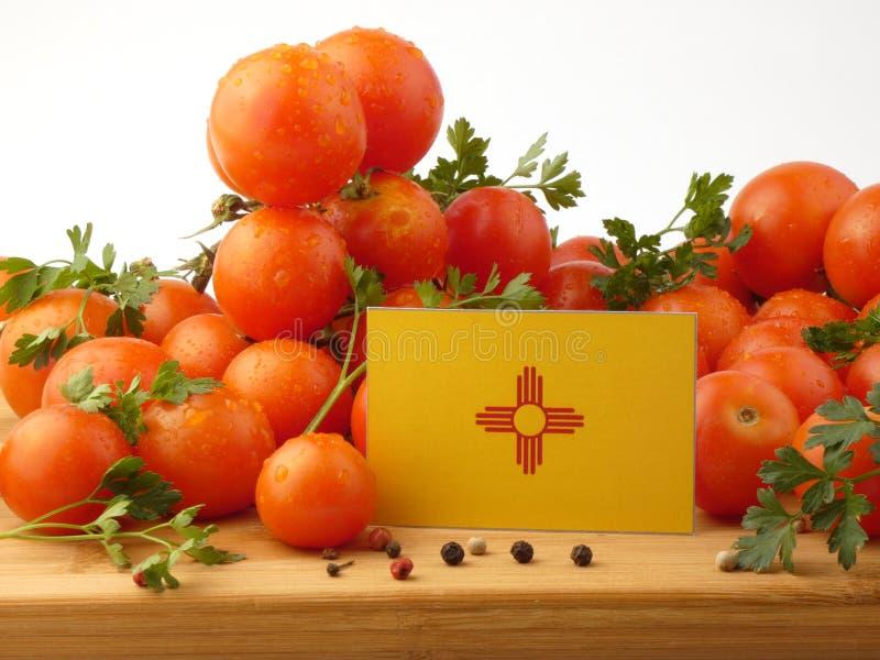 Bandera de New México en un panel de madera con los tomates aislados en un wh fotos de archivo libres de regalías