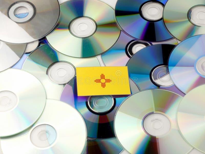 Bandera de New México encima de la pila del CD y del DVD aislada en blanco imágenes de archivo libres de regalías