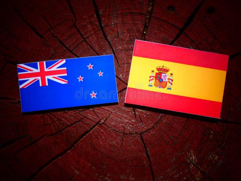 Bandera de Nueva Zelanda con la bandera española en un tocón de árbol foto de archivo