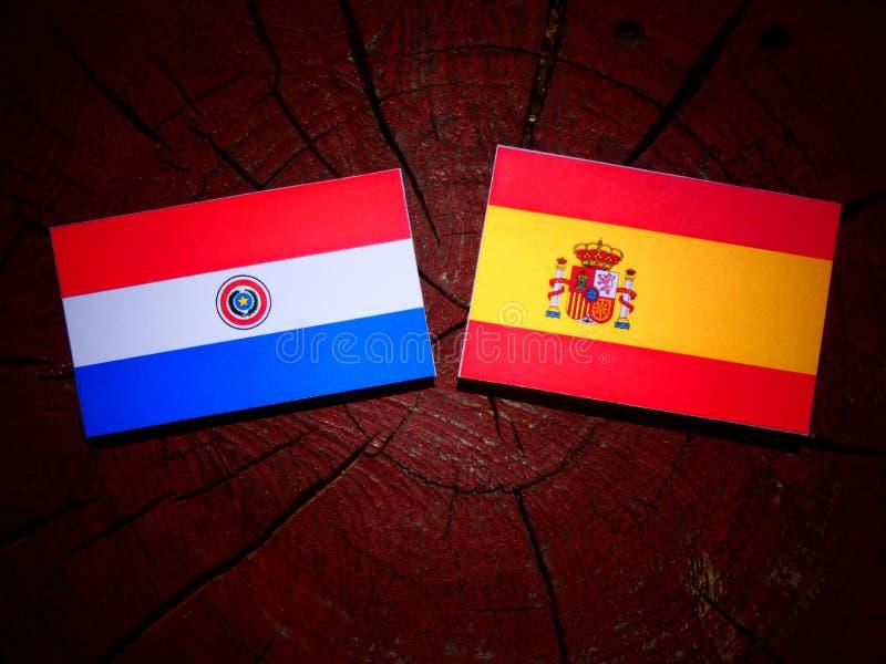 Bandera de Paraguay con la bandera española en un tocón de árbol fotos de archivo