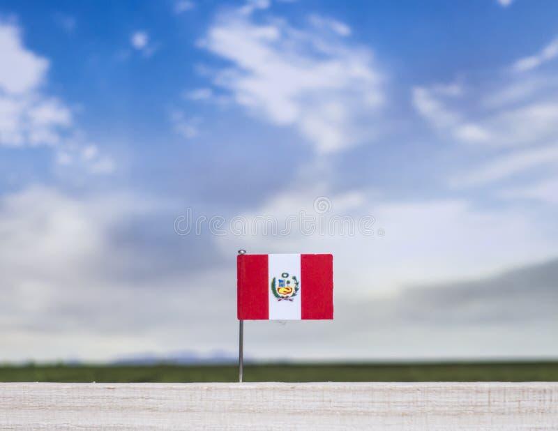 Bandera de Perú con el prado extenso y el cielo azul detrás de él imágenes de archivo libres de regalías